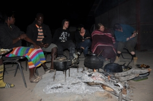 Volunteers sitting around the fire with locals