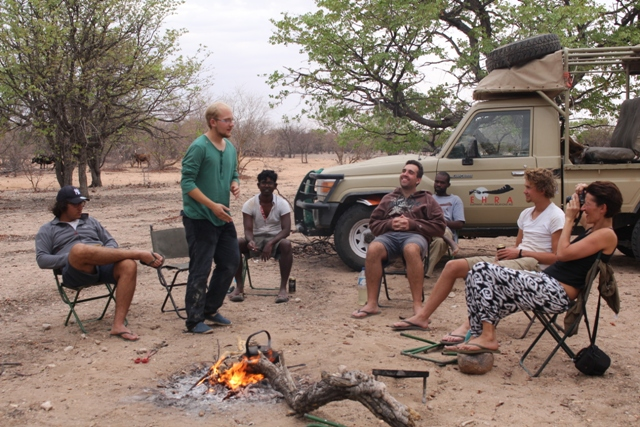 Volunteers sitting around fire.jpg